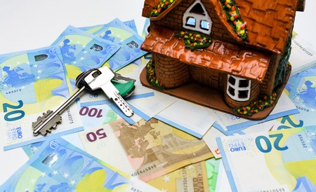 Keys and ceramic house on the background of the euro cash