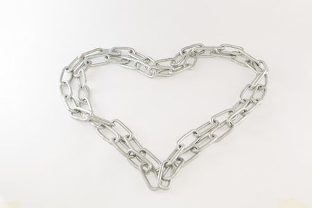 partnership security: Chrome chain forming heart isolated on white
