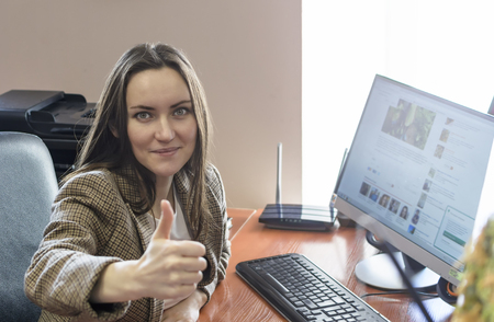 Fun girl office worker showing thumbs up sitting at the computer at work. Work in a ideal - concept