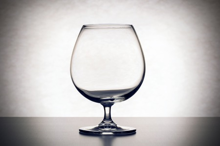 crystal background: One empty brandy glass on white table