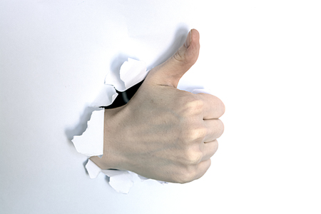 Thumbs up through the hole in paper sheet Stock Photo