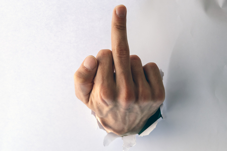 Fuck you - sign on the male hand from a hole in the paper. The middle finger sign.