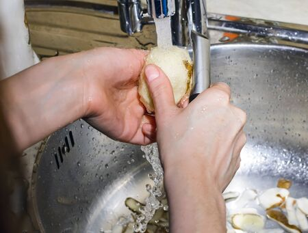 kitchensink: Woman peeling potatoes in the sink under running water Stock Photo