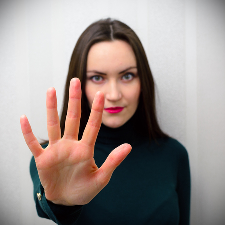 renounce: Girl holding hand like sign No. Negation, discrimination, violence concept.