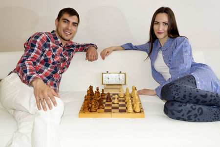 sexes: Relaxed young couple playing chess at home lying on sofa. won - Friendship Stock Photo