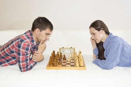 Relaxed young couple playing chess at home lying on sofa. won - Friendship Stock Photo