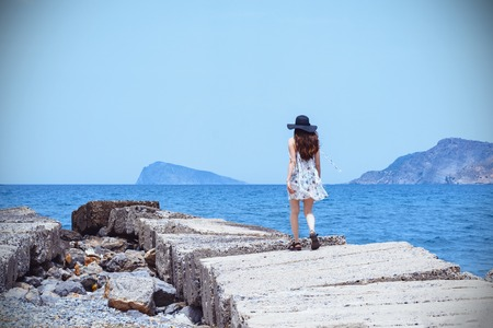 Beautiful, dreamy girl, walks along the stone pier, enjoying the gusts of the wind, long hair,in the white dress and black hat. Concept - travel, of loneliness, come with me, to go to the goal