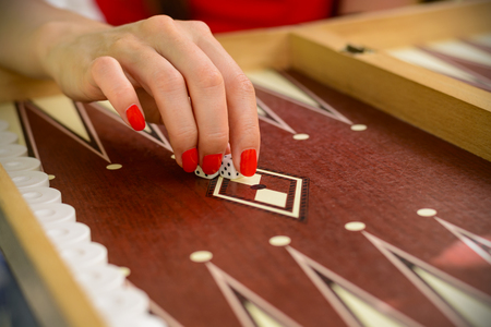 backgammon bone square white dice for gambling with blurred background. woman with red nails is playing backgammon.