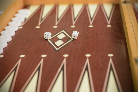 backgammon bone square white dice for gambling with blurred background.