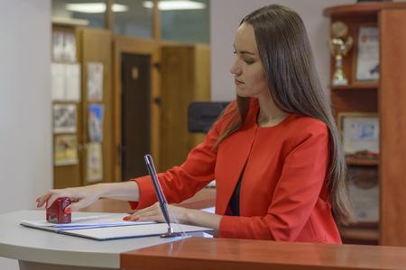 젊은 사업가 또는 공증인, 사무실에서 책상에 스탬프 문서