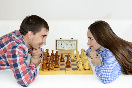 Relaxed young couple playing chess at home lying on sofa.