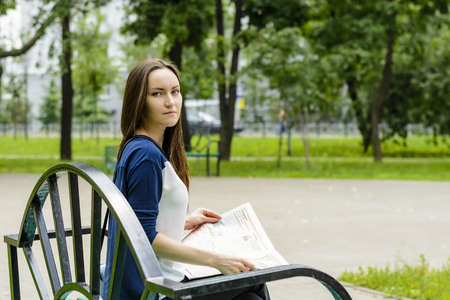 Young business woman reading a newspaper on a bench in autumn Park at lunchtime. tinted