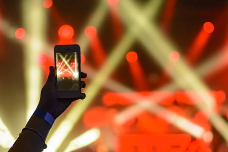 silhouette of hands with a smartphone on the background of the singing artists in the light of the red lights