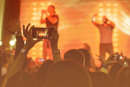 silhouette di mani con uno smartphone sullo sfondo degli artisti di canto alla luce delle luci rosse Archivio Fotografico