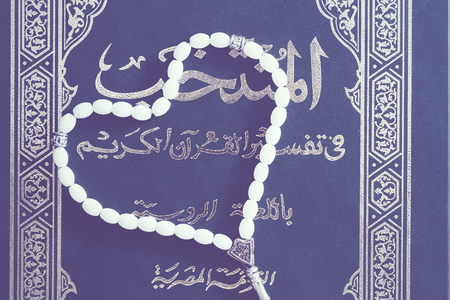 gods: Green Quran Book with white beads in the shape of a heart on a brown wooden background. Prayer Concept. Top view. flat lay. toned