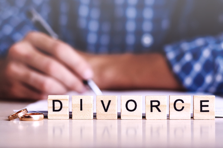 The Concept Of Divorce. The word - Divorce rings in the foreground, a young man in a plaid shirt signed divorce settlement in the background.