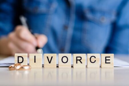 Divorce. Word - Divorce with rings in the foreground, a young woman in a plaid shirt signed divorce settlement in the background. Toned