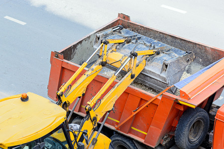 heavy industry: Yellow tractor loading gravel in an orange truck. Technology leads road works. landscaping