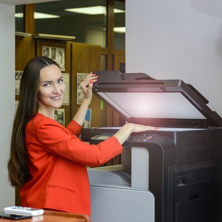 De vrouw in rood pak en lang haar, het glimlachen maakt fotokopieën in bureau voor haar manager. van routinewerk op kantoor met technologie. Stockfoto