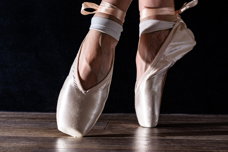 Feet of dancing ballerina on a black background in bright light Stock Photo