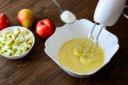 打者またはアップル洋梨のケーキやマフィン、パンケーキの生地を混合します。木製のテーブル c 成分のクローズ アップ。