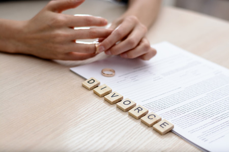 Concept Of Divorce. Word - Divorce with rings in the foreground, a young woman in a plaid shirt signed divorce settlement in the background.