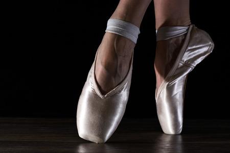 Voeten van dansende ballerina op een zwarte achtergrond in fel licht