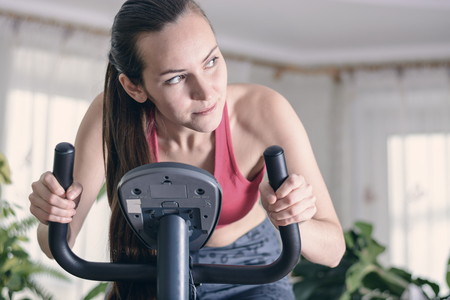 European woman training cardio work-out at home on exercise bike. Concept for weight loss. Motivated and focused young girl. Imagens - 92543049