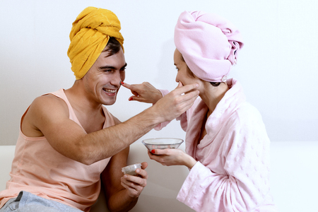 Fun loving couple cares for the skin. Sitting on the couch in towels and cause each other clay mask on the face. Health care, beauty and youth. Funny scenes of family life. Archivio Fotografico