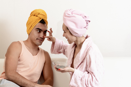 Fun loving couple cares for the skin. Sitting on the couch in towels and cause each other clay mask on the face. Health care, beauty and youth. Funny scenes of family life. Stock Photo