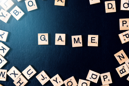 Word GAME with wooden letters on black Board with dice and letter in the circle.