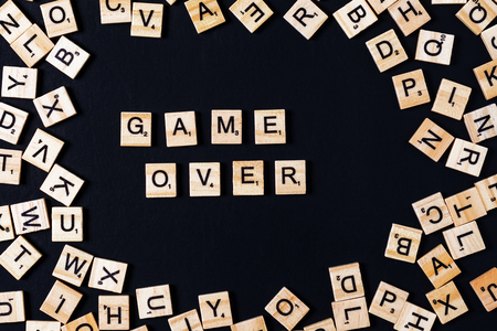 Word BOARD GAME with wooden letters on black board and letter in the circle. Stock Photo