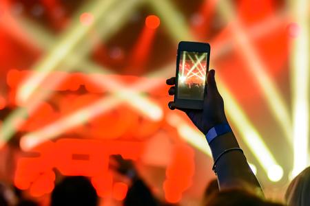 赤い光の中で歌うアーティストの背景にスマートフォンで手のシルエット