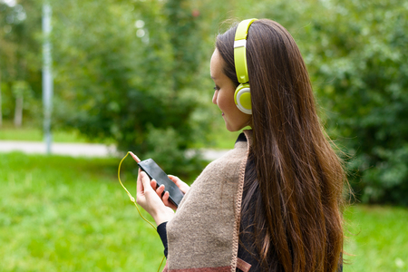 Happy smiling girl listening to music on headphones in Park closeup. The concept of rest from the noisy city Stock Photo