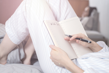Close-up of a young woman in home pajamas lying in bed and making a wish list. concept of planning, goals, future, mode day