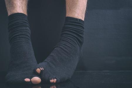 feet of the poor debtor's in black holey socks on a black background