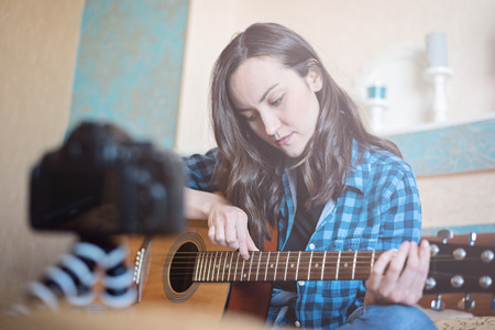 Blogger girl records on DSLR camera tutorial vlog for playing acoustic guitar. Stock Photo - 99206227