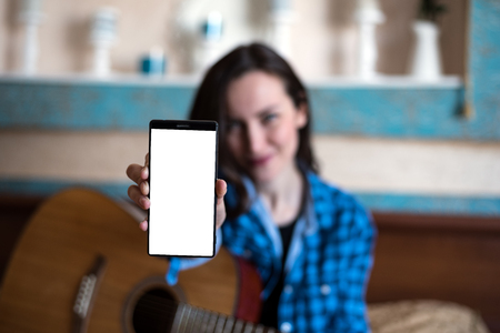 Young woman with acoustic guitar shows hand with smartphone with copy space, mock up. the blogging concept.