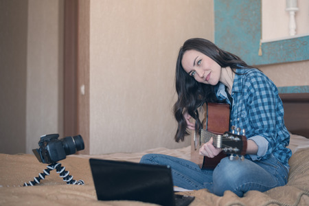 Young girl playing acoustic guitar in the room.