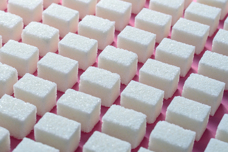 Cubes of refined white sugar the correct geometric shape on a pink background. Minimalistic abstract screensaver
