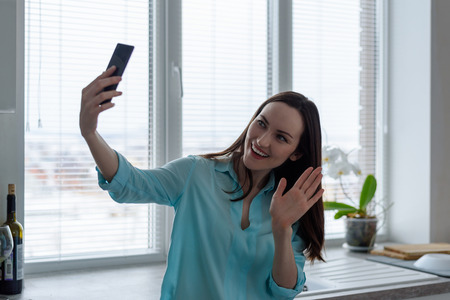 young brunette communicates online through a smartphone in the kitchen, waving a greeting symbol