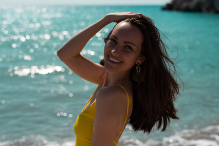 Large portrait in the hard light of the bright sun of a young woman on the sea in a yellow swimsuit, real life. Stock Photo