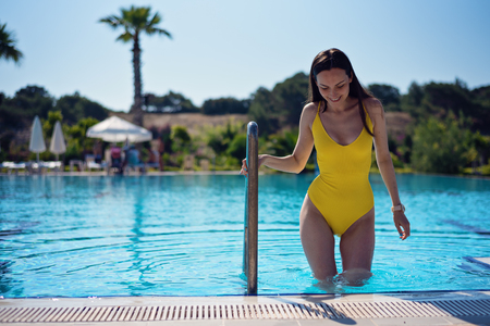 frontal portrait of a sexy woman in a yellow body comes out of the pool holding onto the handrails. mouth-watering thighs