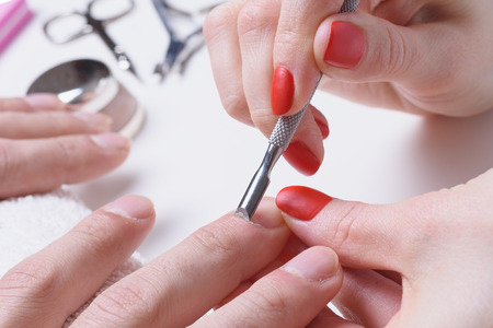 Men's manicure. hands of the beautician treated cuticle of male hands using pusher, scraper. Stock Photo