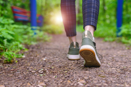 Close-up of women's legs in green sneakers and pants in a cage go on a forest road. HLS, walk in the open air. Foto de archivo