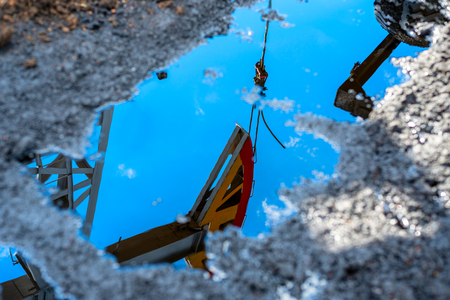 Reflection of the oil pump in a puddle of spilled crude oil. Environmental pollution, ecology, disaster