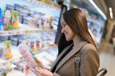 Smiling business woman in a jacket in the store holding a package of Turkey, reading the composition.