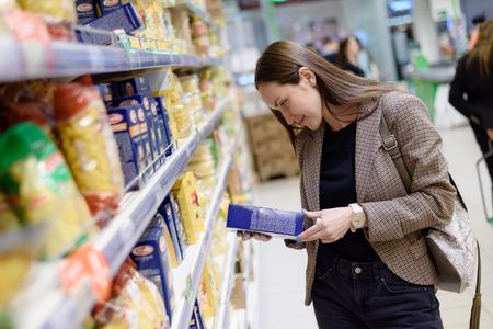 sonriente mujer de negocios en una chaqueta en un supermercado elige un paquete de la pasta