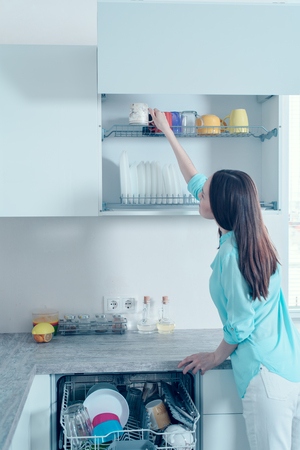 Rear view of a woman in a turquoise shirt puts clean glasses on the shelf of the dishwasher.