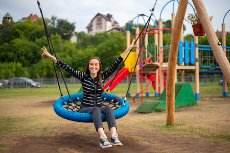 Young happy woman on hanging swing in Park smiling hands up, concept of freedom, weekend, childhood. 스톡 콘텐츠